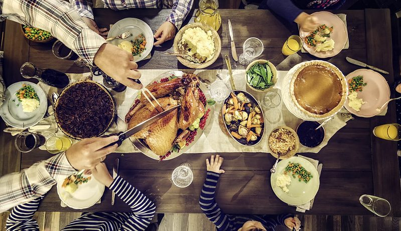 Family gathers around Thanksgiving table